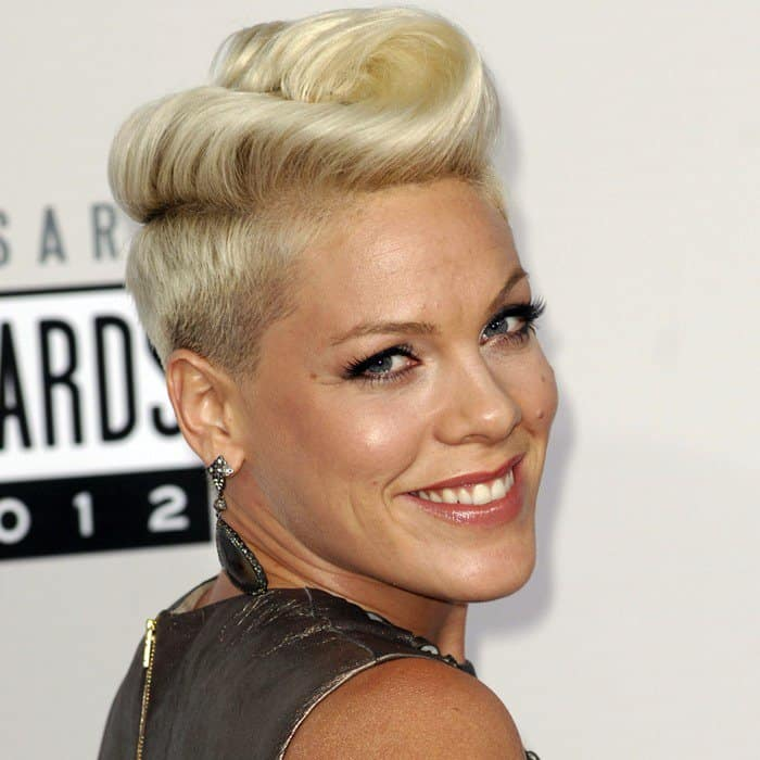 A short, swirly platinum blonde hairdo, large silver drop earrings, and a silver bracelet completed her look