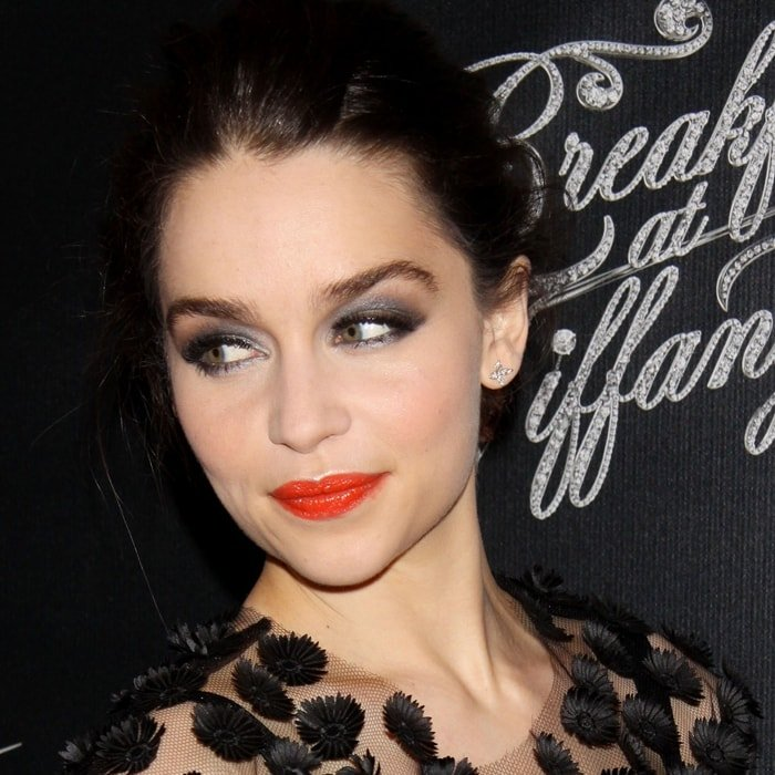 Emilia Clarke with red lips and her black hair pulled back