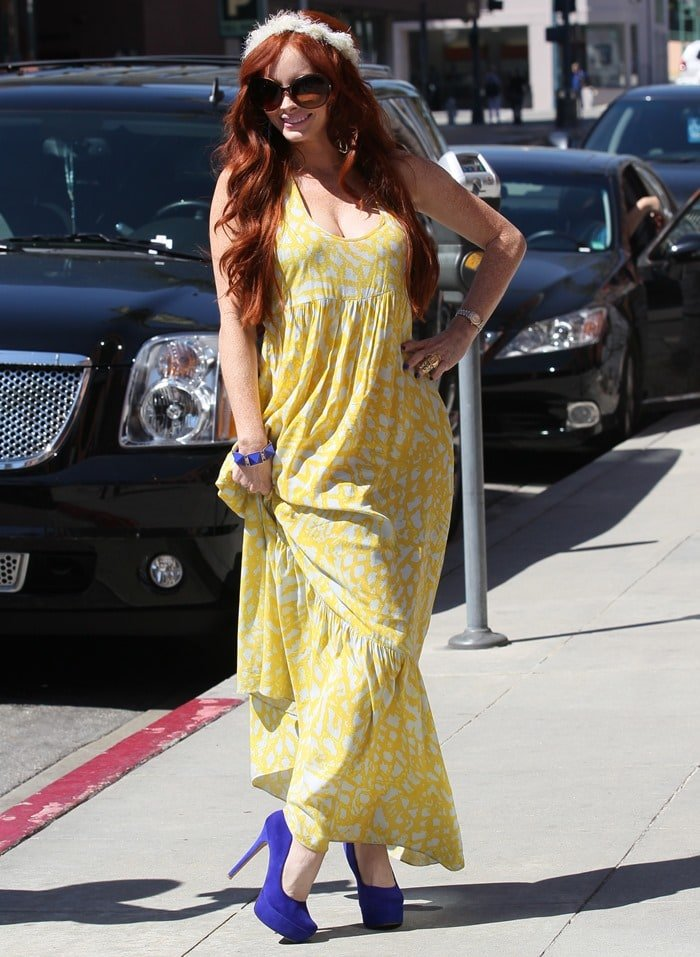 Phoebe Price sported a bright yellow maxi dress paired with an interesting goddess-like headband and blue accessories, including a blue bracelet and a pair of blue pumps