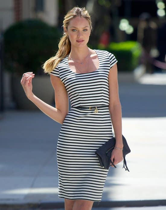 The striped figure-hugging dress styled with a slim belt, a large black clutch, and a pair of low-heeled pumps