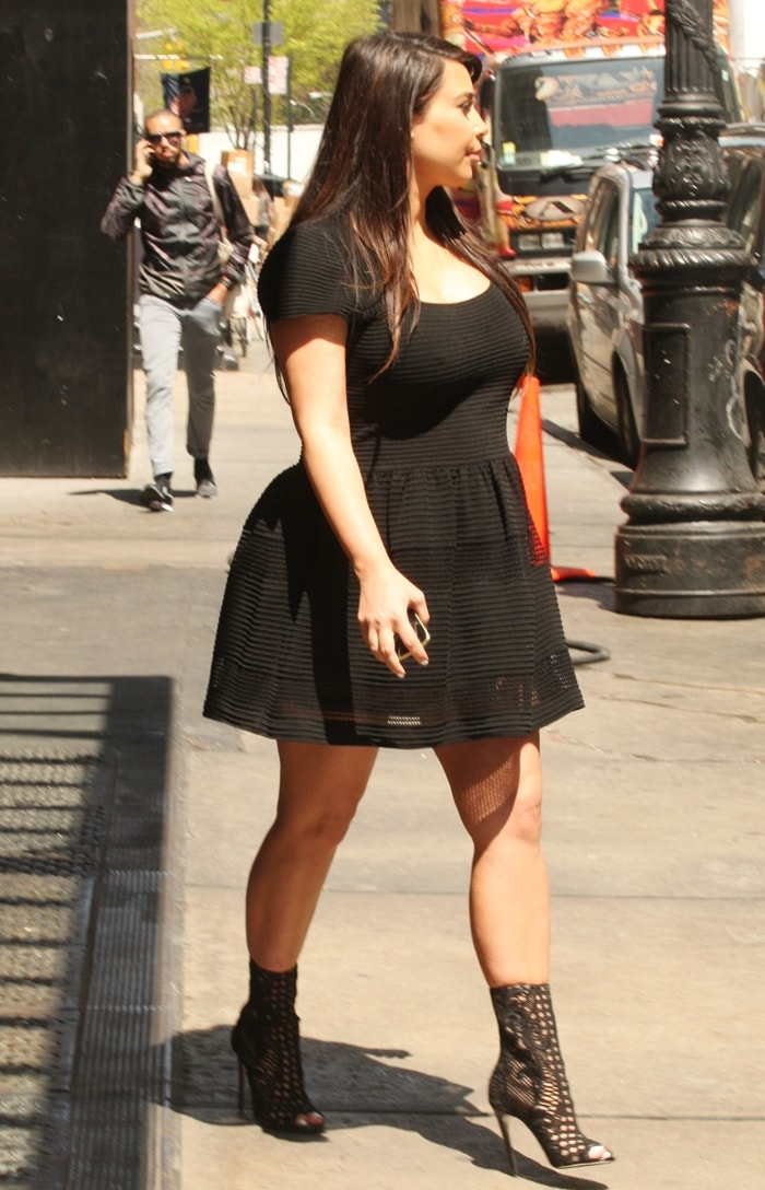 Kim Kardashian wears a simple short black dress and cutout ankle boots
