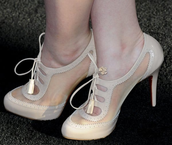 Joey King wearing nude lace-up shoe boots are from Christian Louboutin