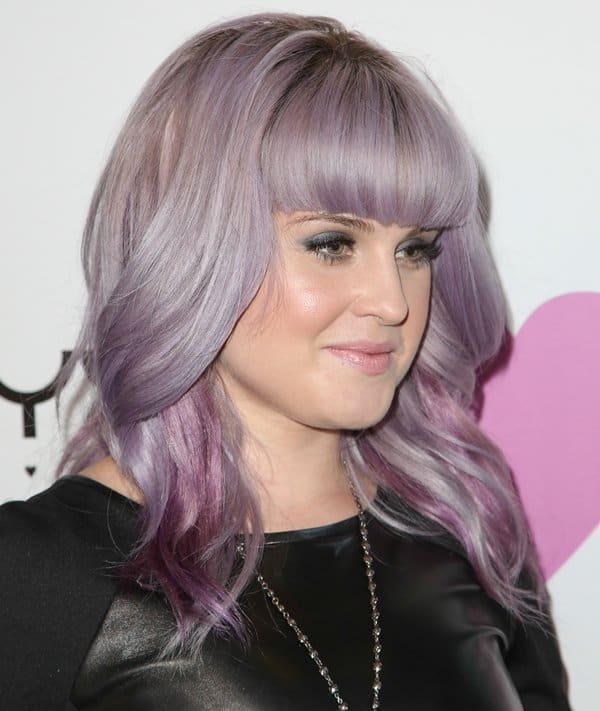 Purple-haired Kelly Osbourne in a black leather dress