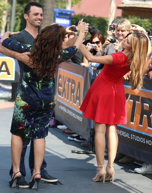 Maria Menounos having fun in a red dress on the set of Extra in Los Angeles