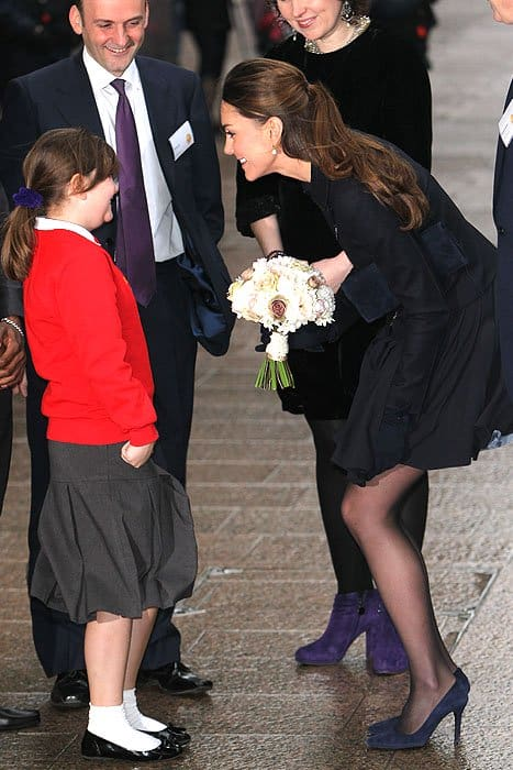 Kate Middleton talking with a school girl while taming a windblown skirt at the charity Place2Be in Canary Wharf in London, England on November 20, 2013
