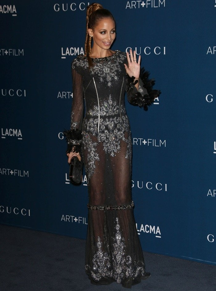 Nicole Richie shows off her underwear in a sheer dress by Dolce & Gabbana featuring silver beading and feather-and-bedazzled cuffs