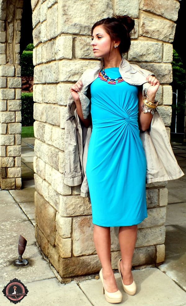 Cara wears a blue knotted dress with a statement necklace