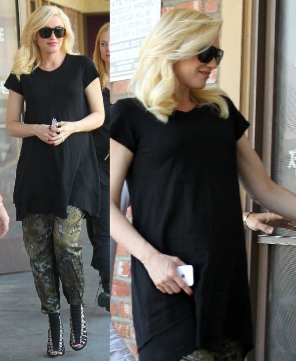 L.A.M.B. founder and designer Gwen Stefani wearing a black maternity dress over a pair of loose olive green pants and a strappy pair of high-heeled sandals