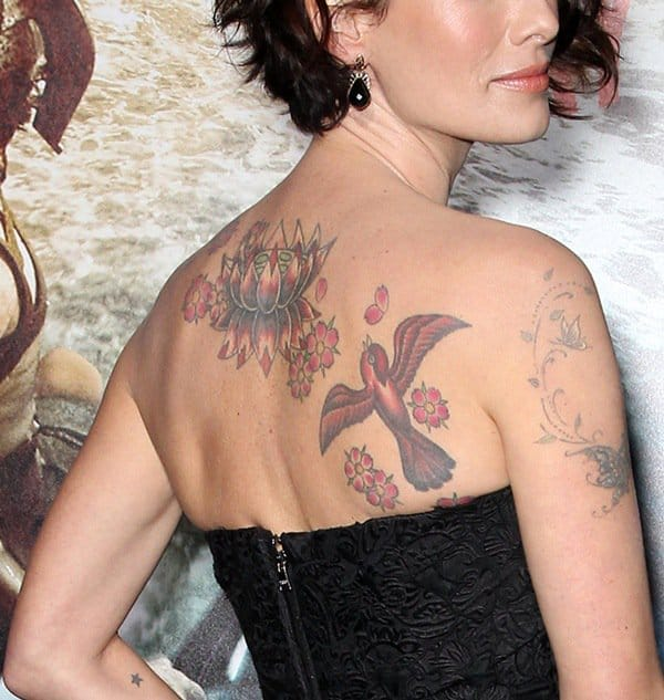 Lena Headey showing off her lotus flower and sparrow tattoos