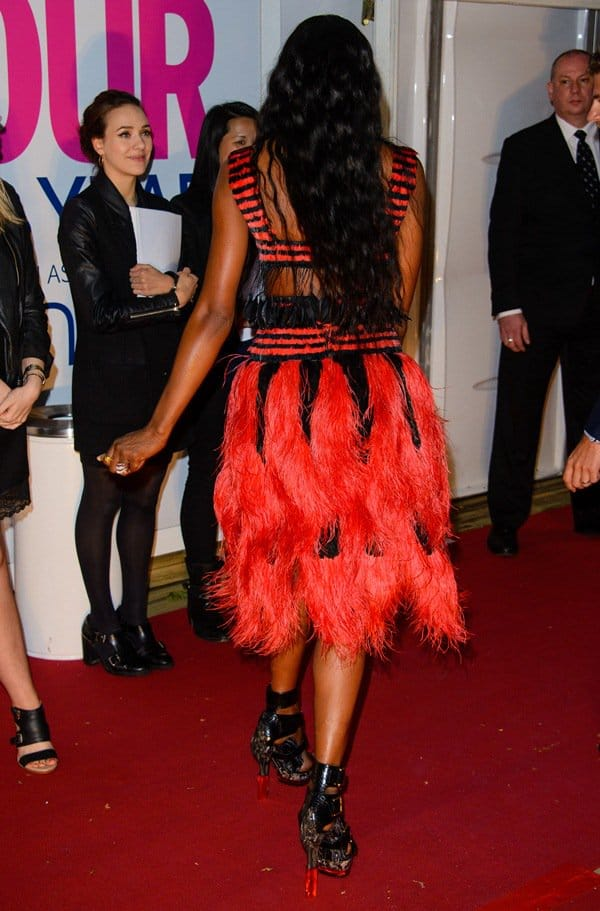 Naomi Campbell's dress features a bold striped design with fringe feathers on its crop top and a fully feathered skirt