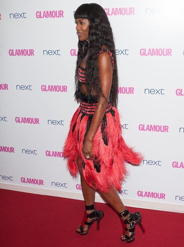 Naomi Campbell wearing a cocktail dress and gladiator sandals by Alexander McQueen