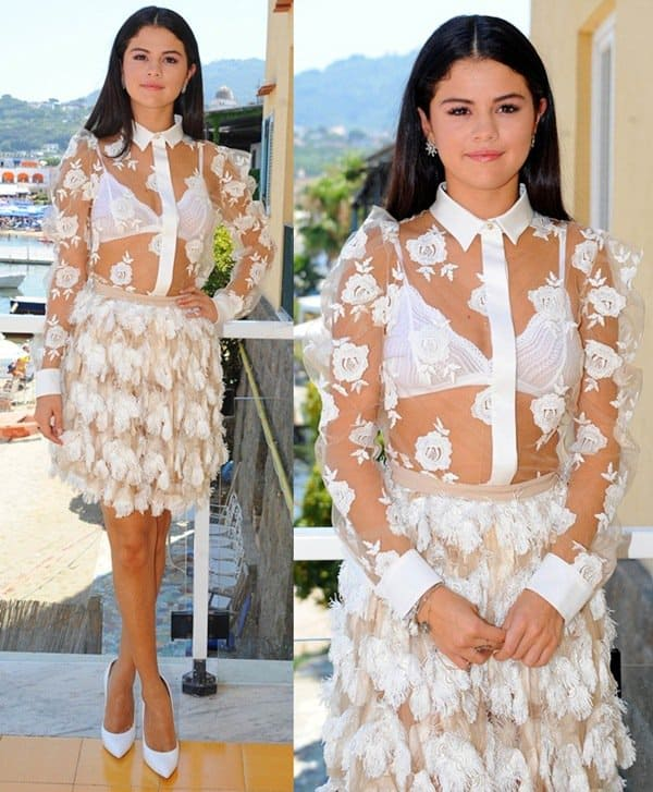 Selena Gomez wearing a Bluemarine outfit consisting of a sheer white shirt and a feather-embellished skirt