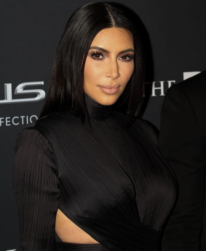 Kim Kardashian sported a toned down floor-length crepe gown from Balmain that for once did not show off her infamous cleavage