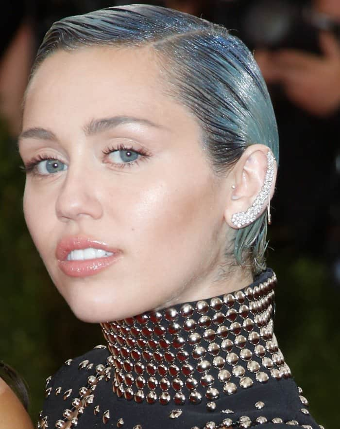 Miley Cyrus donned a black gown from the Alexander Wang Fall 2015 collection featuring skin-baring cutouts and all-over silver studs