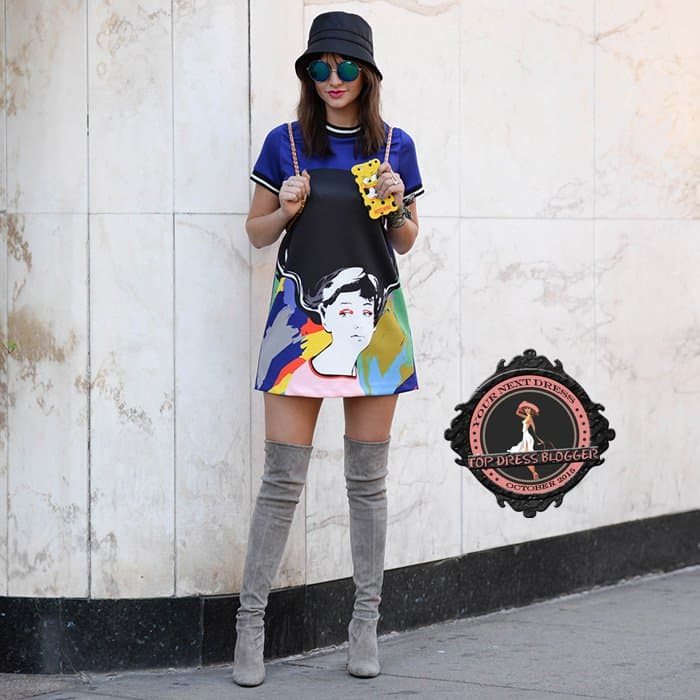 Alexandra in a statement-making colorful painted mini dress with thigh-high boots