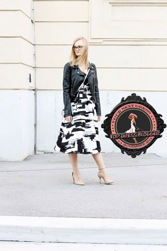 Casey wears a maxi dress with black leather jacket and nude asymmetrical pumps