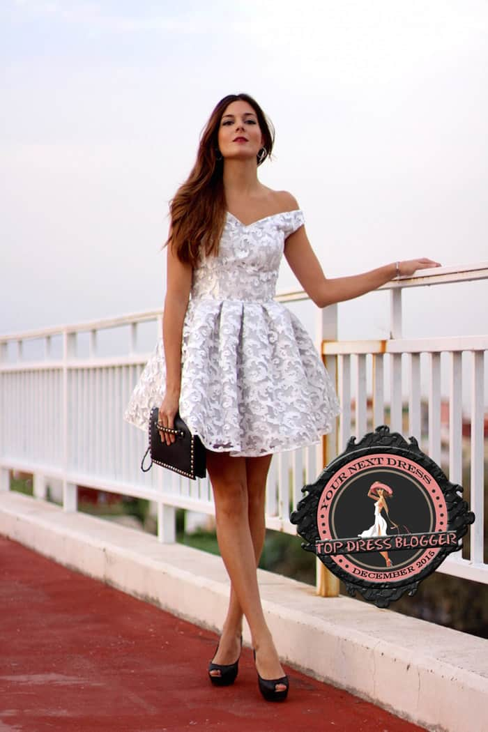 Marianela in a flirty yet elegant white lace dress with black peep-toe pumps