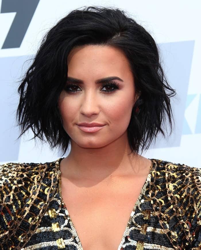 Demi Lovato wearing black and gold Balmain dress