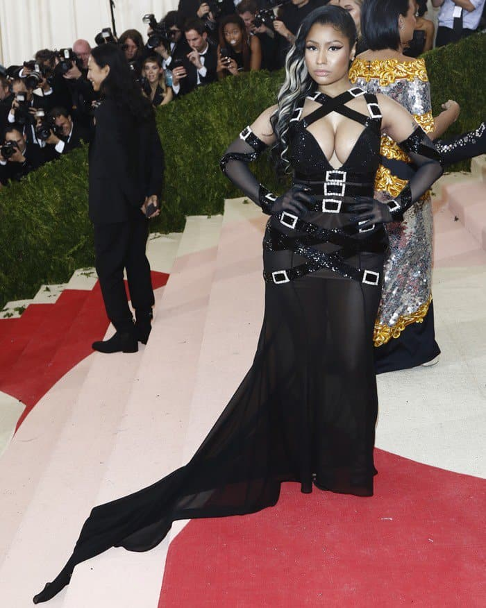 Nicki Minaj'smassive cleavage almost spilled out of her bondage-inspired black gown