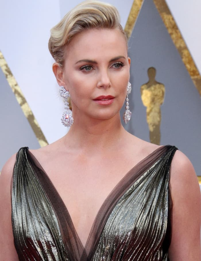 Charlize Theron wearing a Christian Dior gold lamé gown and Chopard diamond drop earrings at the 2017 Academy Awards