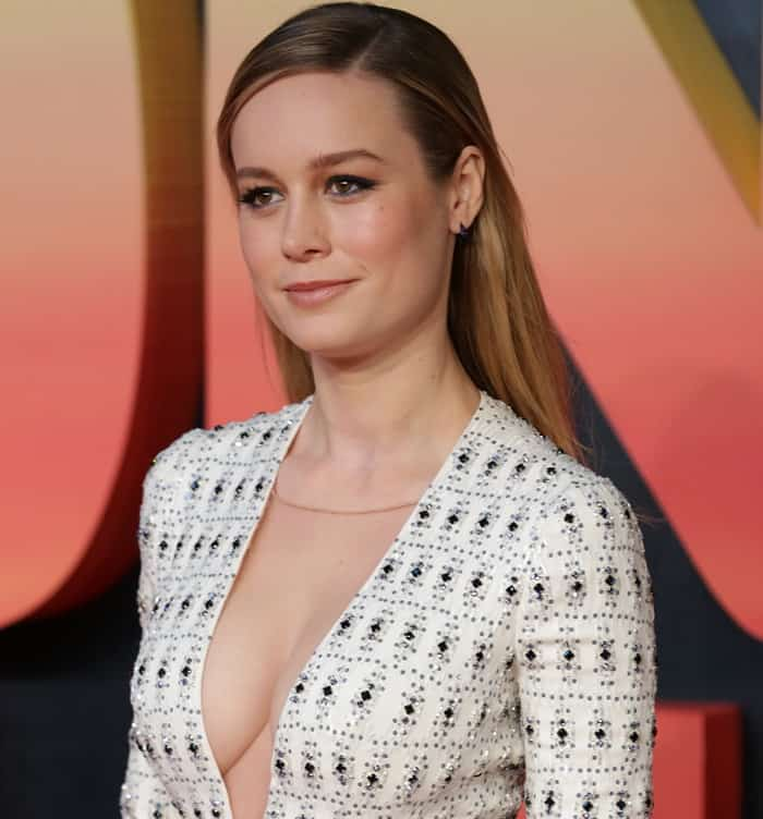 Brie Larson in a cream tiered gown featuring a plunging neckline