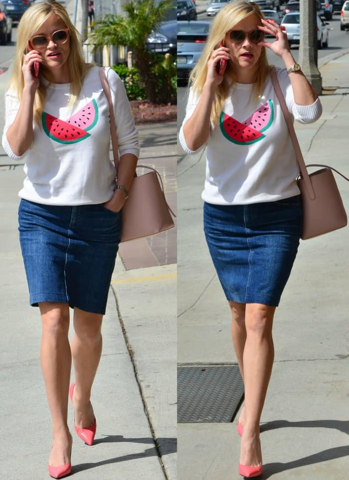 Reese Witherspoon wearing the Watermelon Sweater from Draper James, a denim skirt, and pink pointy-toe pumps