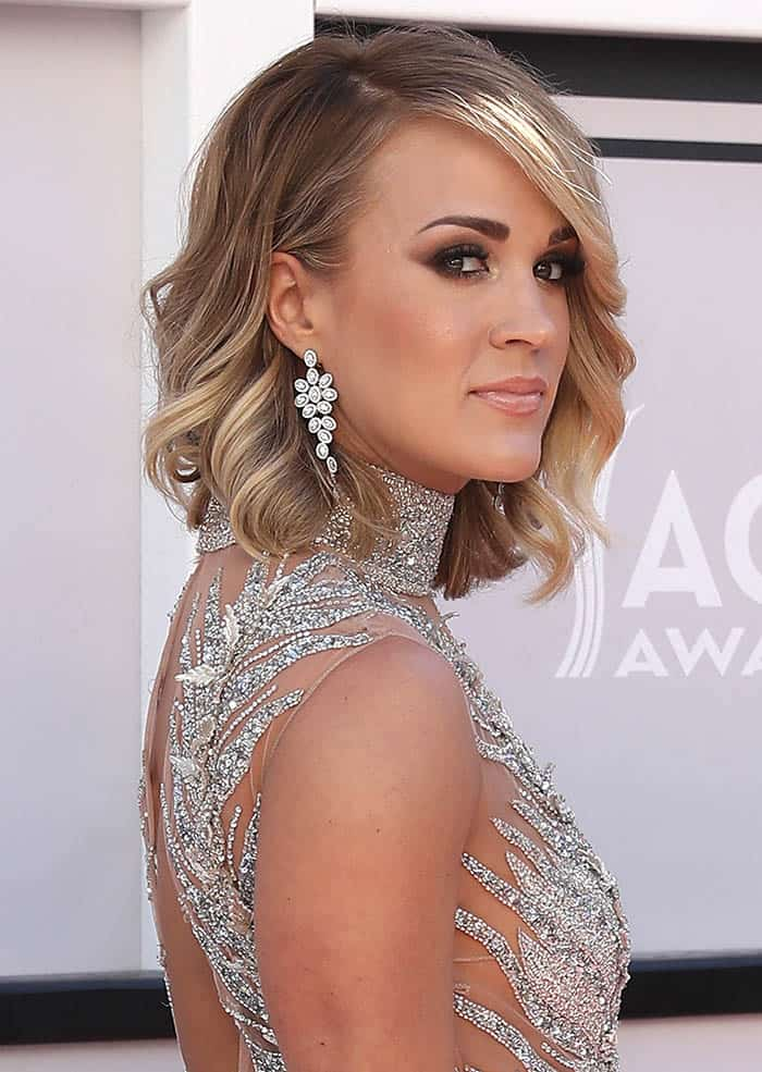 Carrie Underwood accessorized with a pair of Harry Kotlar diamond earrings and some rings