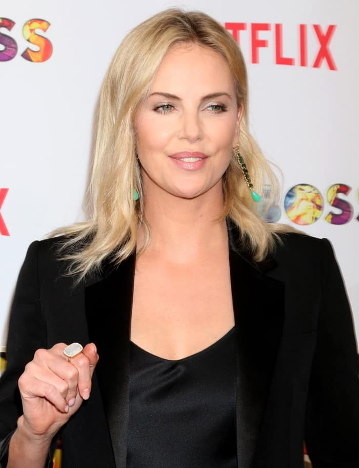 Charlize styles her classy ensemble with minimal makeup and emerald green drop earrings