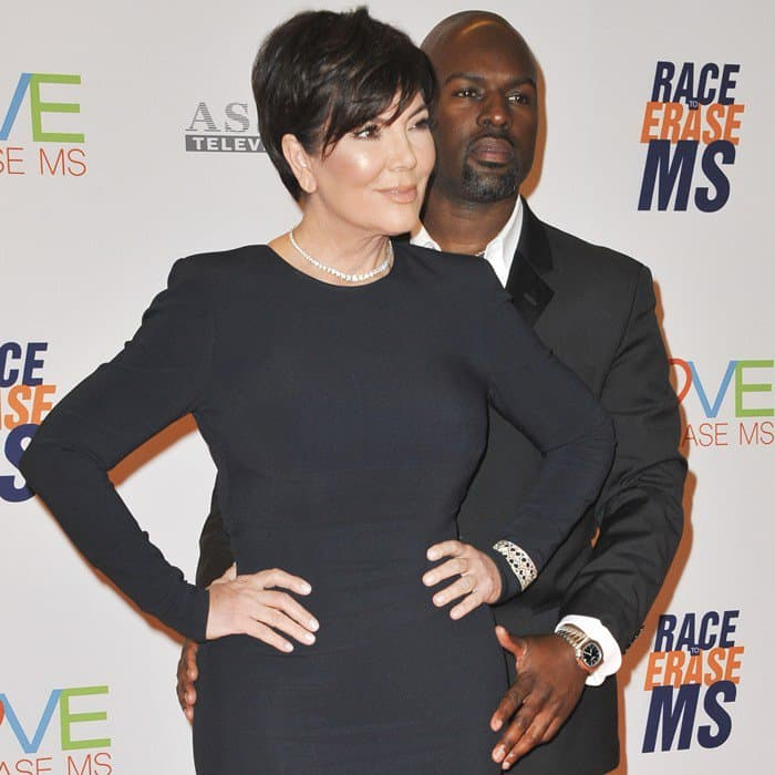 Kris Jenner accessorized with a wide metal bracelet over the sleeve on her left arm, a glittering diamond necklace, and stud earrings