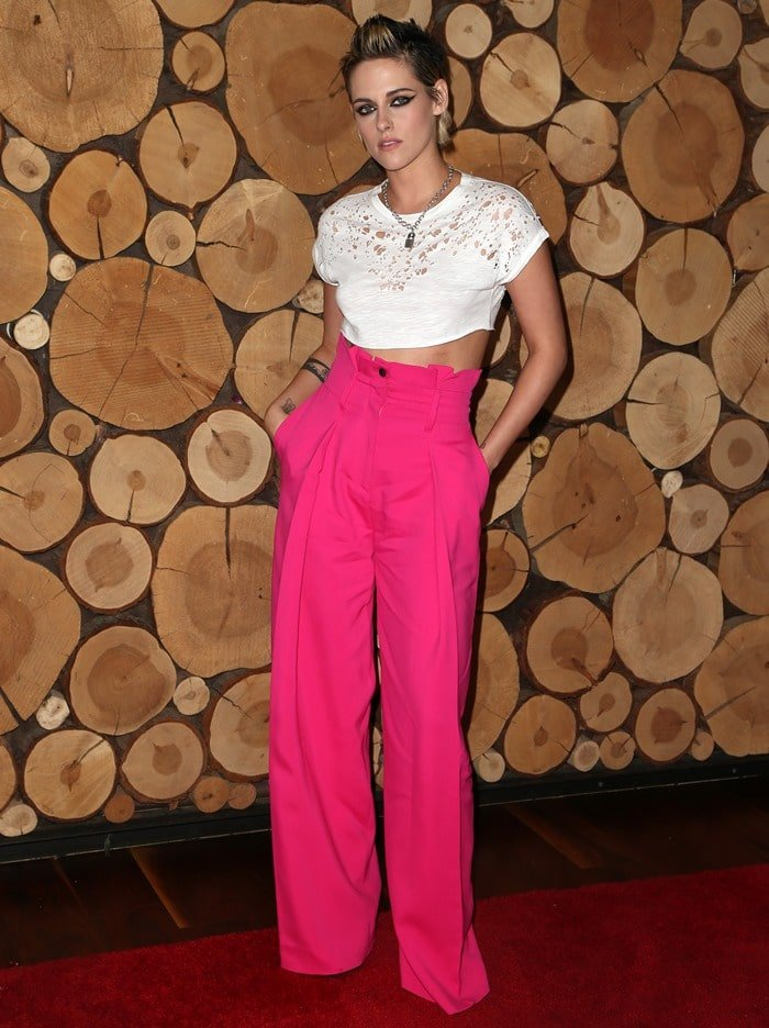 Kristen Stewart in bright pink pants from Zuhair Murad's Pre-Fall 2017 collection paired with a white Murmur Spring 2018 lace crop top