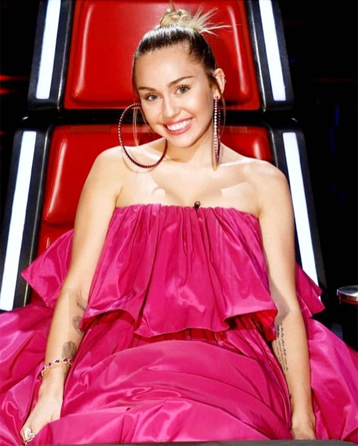 """Miley Cyrus' Instagram pics of her wearing an Agatha Ruiz De La Prada spring 2018 pink tiered-ruffle strapless dress and pink satin chunky platform sandals on a live episode of """"The Voice"""" on November 21, 2017."""