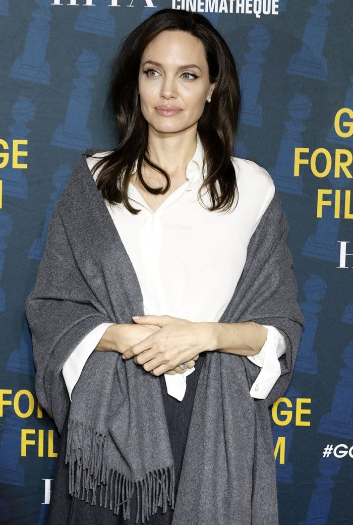 Angelina Jolie wearing a white oxford shirt and a grey scarf