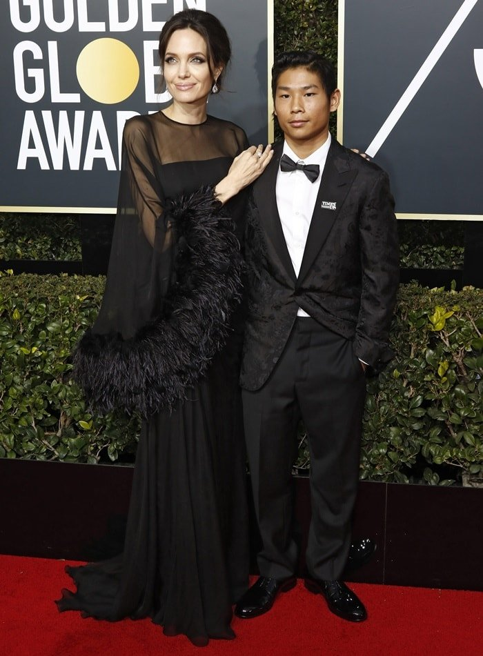Angelina Jolie posed for photos with her son Pax Jolie-Pitt, 14, while walking the red carpet at the 2018 Golden Globe Awards held at the Beverly Hilton Hotel