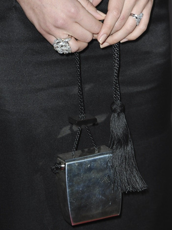Margot Robbie showing off her rings and THE ROW's resin evening case clutch bag