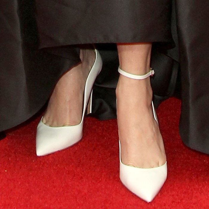 Closeup of the white Aquazzura 'Dolce Vita' ankle-strap pumps on Taryn Manning.