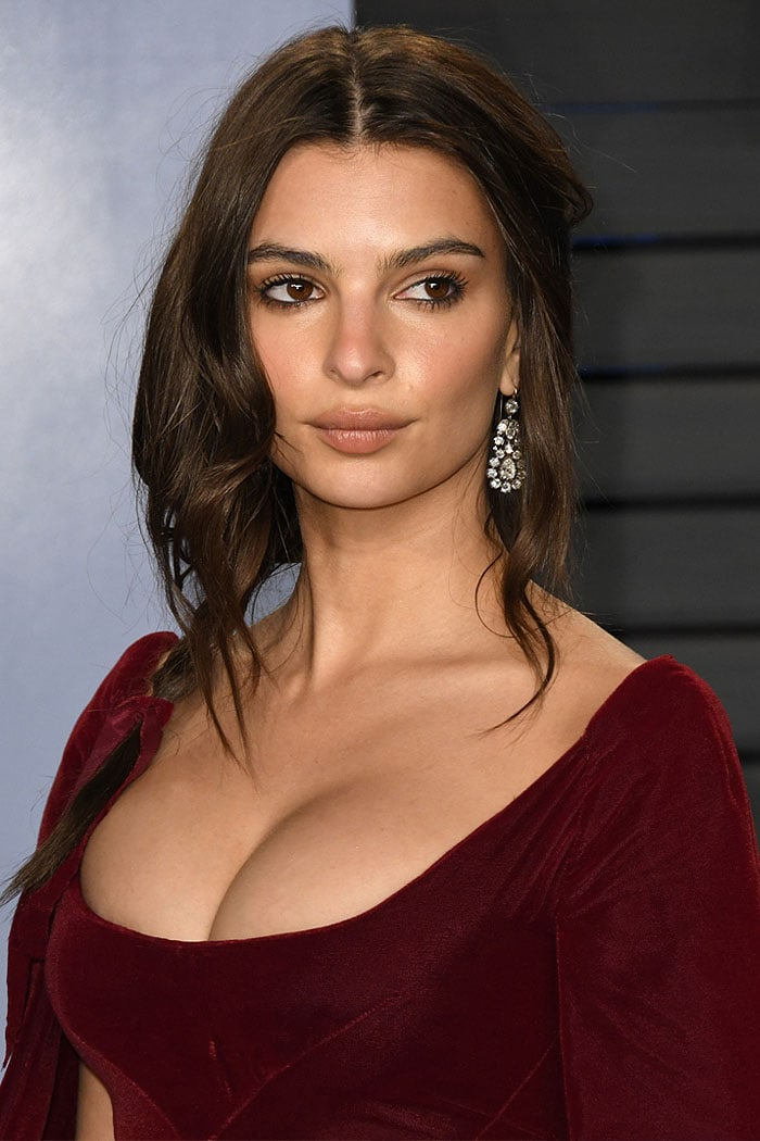 Emily Ratajkowski's cleavage in a Zac Posen wine-red caped dress