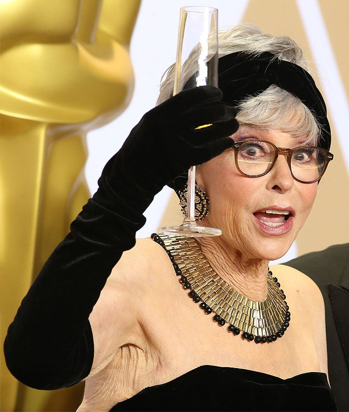 Rita Moreno holding champagne in the press room at the 2018 Academy Awards.