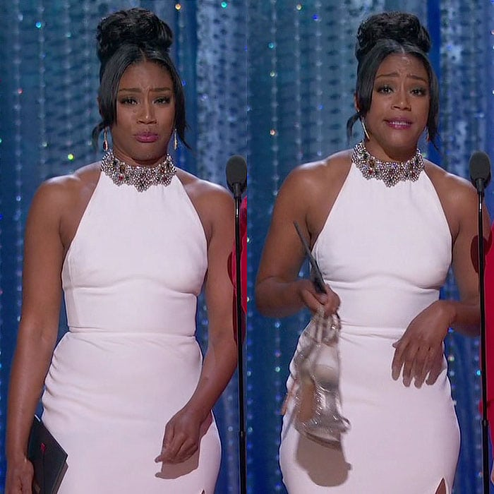 Tiffany Haddish wearing her white Alexander McQueen dress and carrying her Stuart Weitzman 'Nudist' sandals while presenting during the 2018 Oscars.