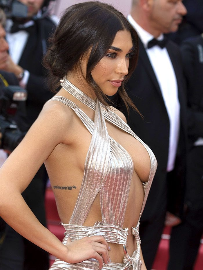 Chantel Jeffries baring boobs in a silver dress held by a ring.