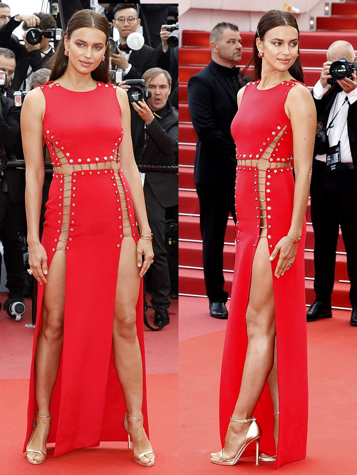 Irina Shayk in a red Atelier Versace chained double-split dress, gold Versace ankle-strap sandals, and Chopard jewelry.