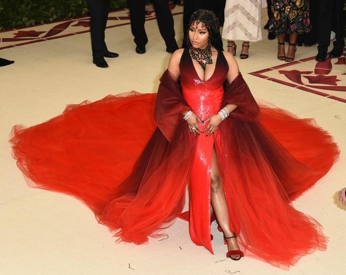 Nicki Minaj in a custom Oscar de la Renta red gown, tulle coat, rosary headpiece, and Le Silla 'Gaga' fur sandals.