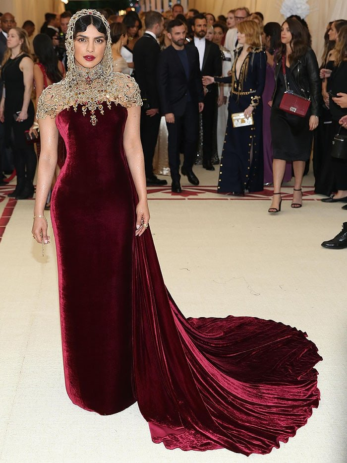 Priyanka Chopra in a Ralph Lauren Collection burgundy velvet gown and a jeweled hood headpiece.