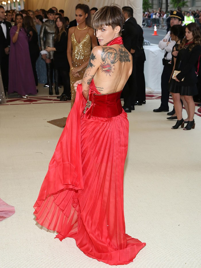 Ruby Rose wearing a Tommy Hilfiger red pleated dress with a velvet sash, gold Jimmy Choo
